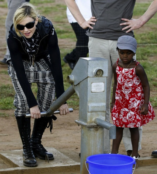 Madonna pumps water from a hand pump next to her adopted Malawian child Mercy James during a visit to Gumulira village